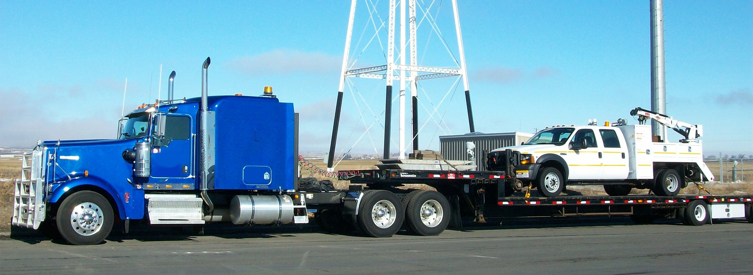 Blue semi with black step deck tailor hauling and electrical truck