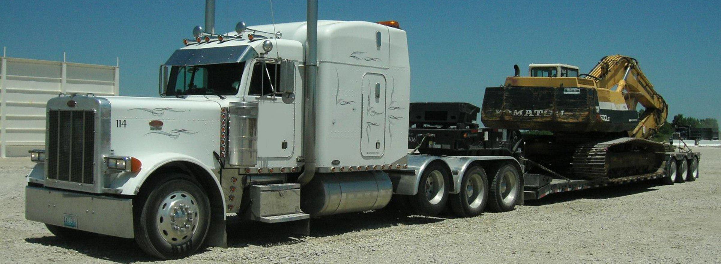 White semi with step deck trailor hauling a crane