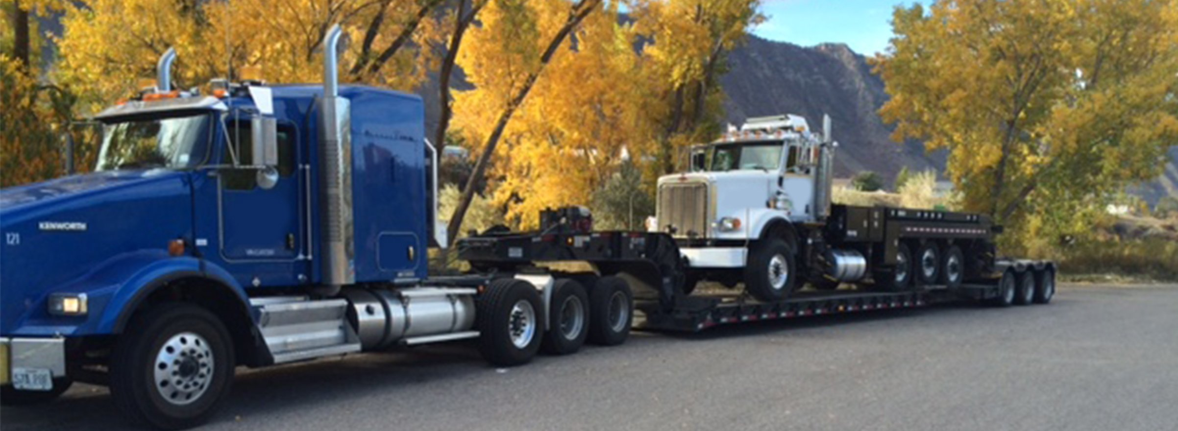 Blue semi hauling a white dump truck