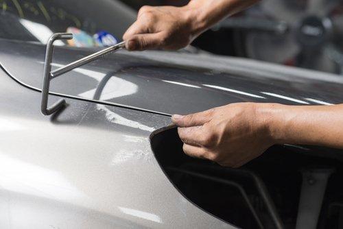 Un carrozziere ripara il cofano di un auto d'epoca