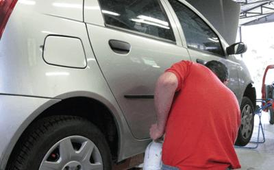 Un carrozziere ripara i danni da bozzi digrandine