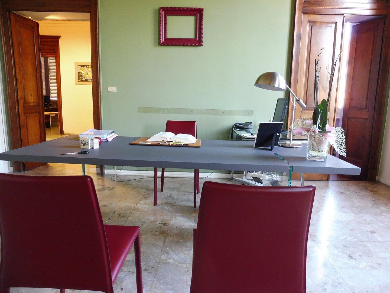 sala riunioni con tavolo grigio e sedie rosse