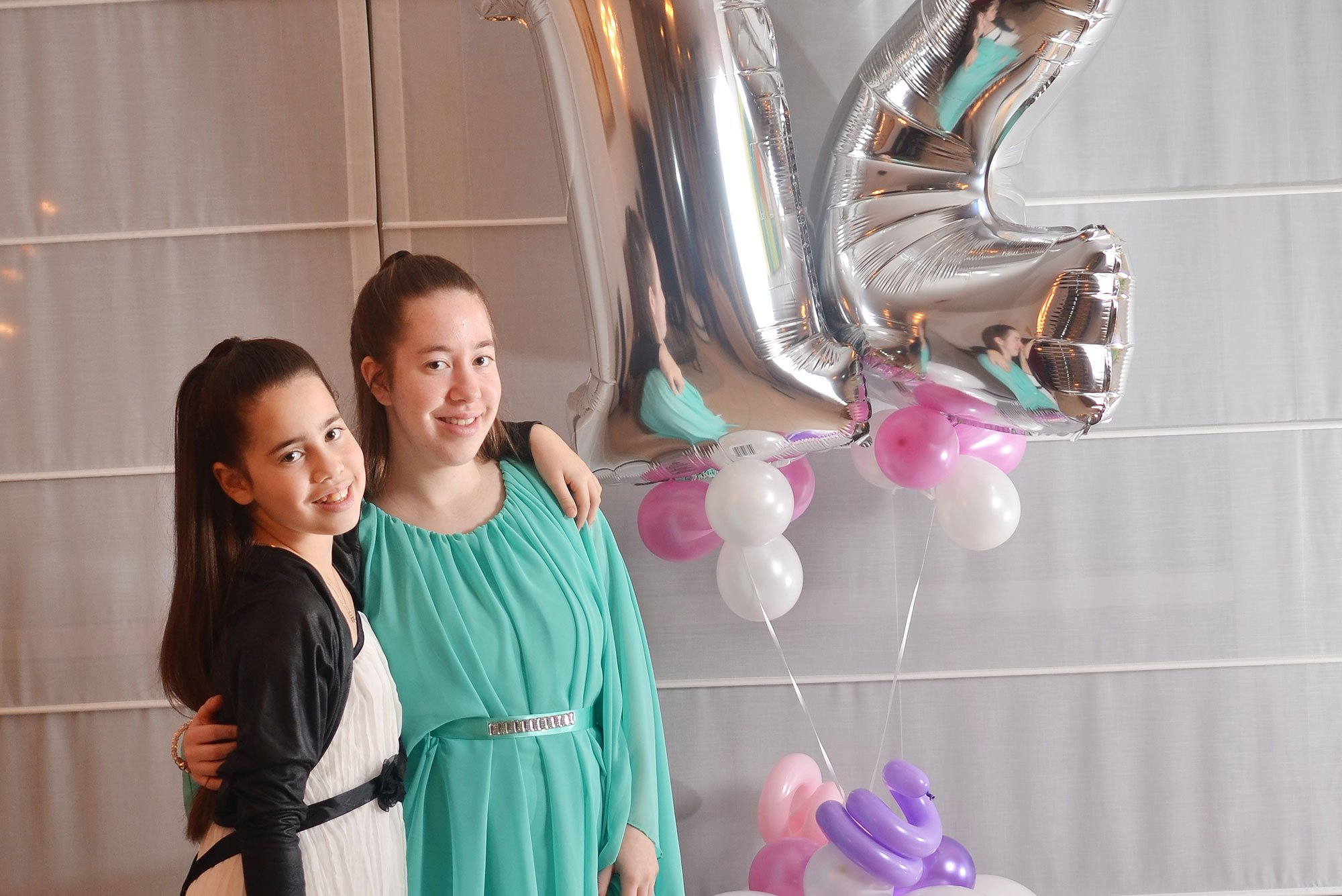 Young girls celebrating together with balloons