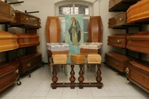 esposizione di bare in legno con al centro immagine sacra