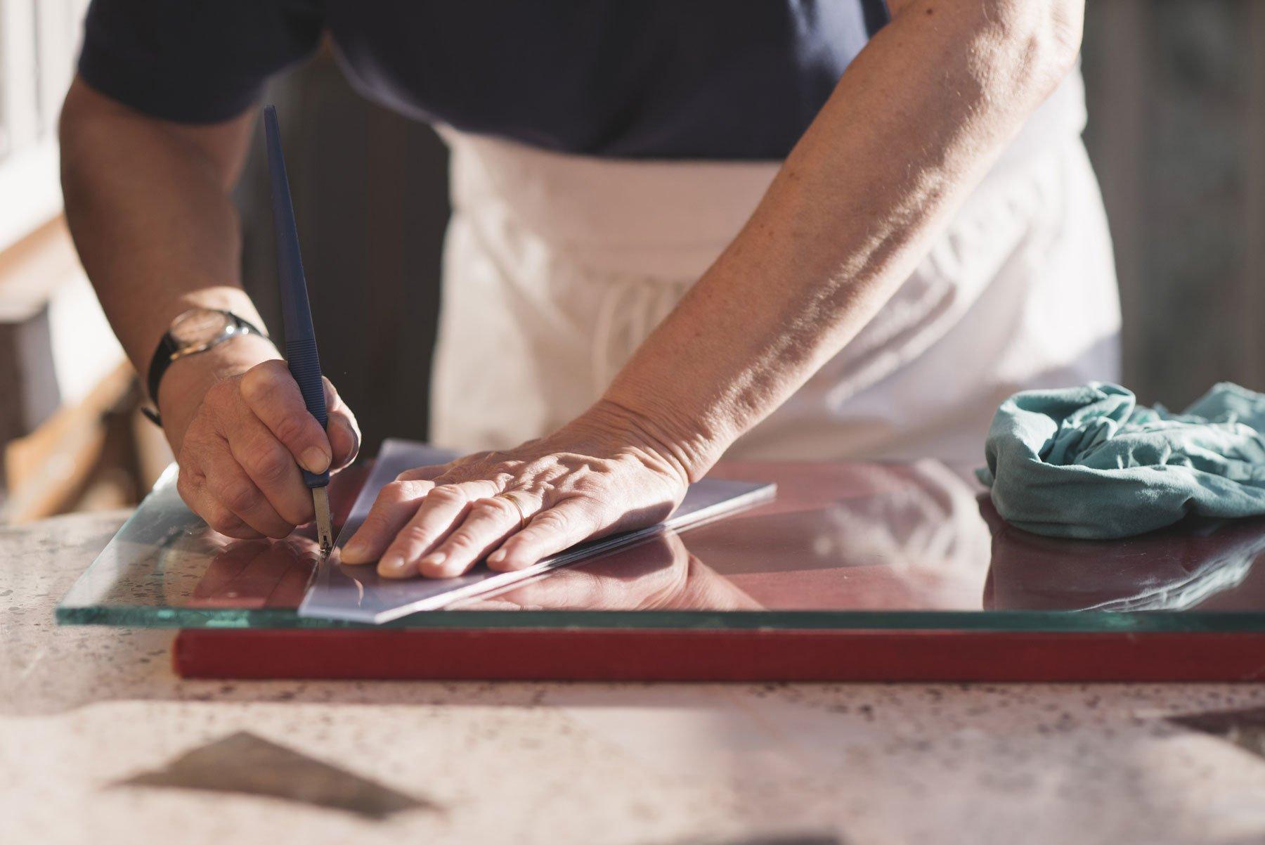 Mani lavorano su lastra di vetro con punta di diamante