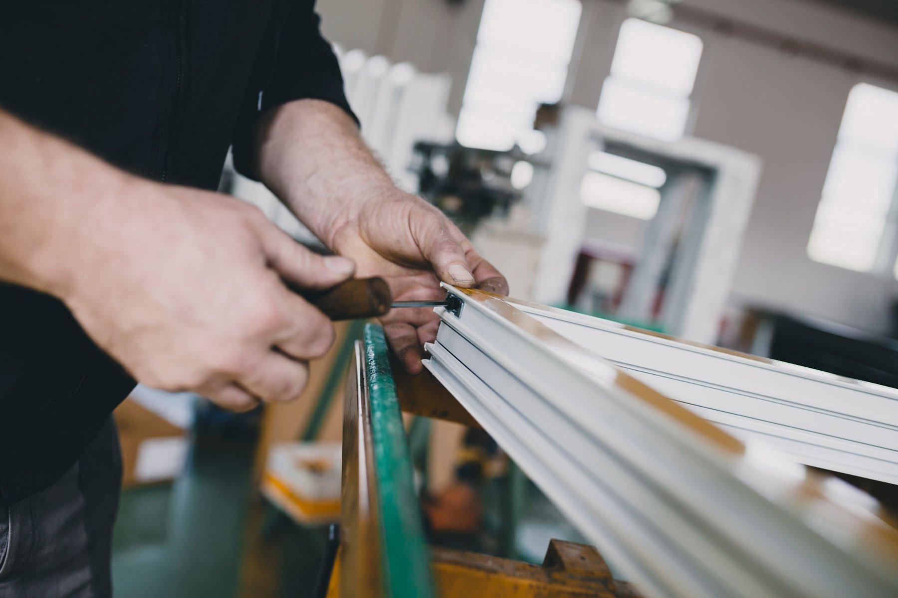 Mani che sistemano un telaio in PVC