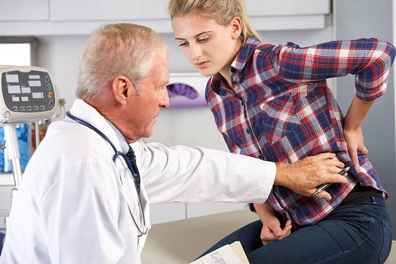 Teenage girl visits doctors office with back pain