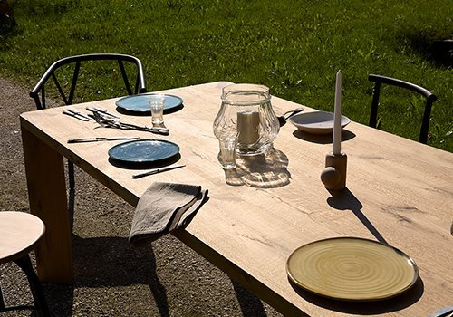 Tavola di legno con piatti,coperti e due candele