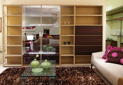 una sala con un divano e un mobile in legno a due ante con effetto a  specchio