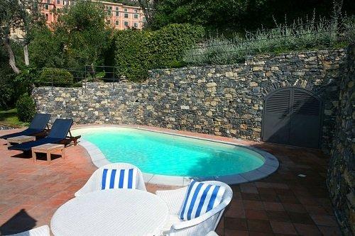 vista di una piscina con tavolo e sedie di plastica bianca