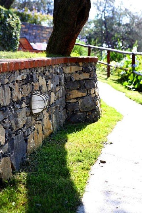 vista di un muretto in pietra lungo un percorso camminabile
