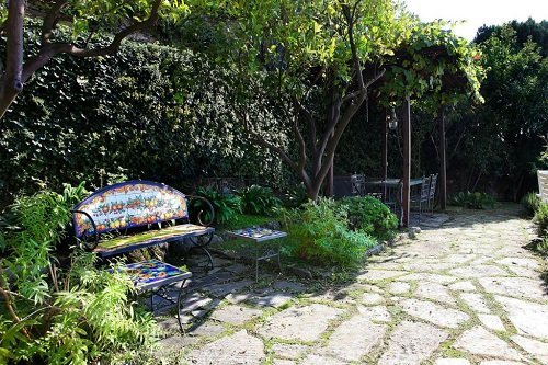 vista di zona relax con panchina e tavolo a lato giardino