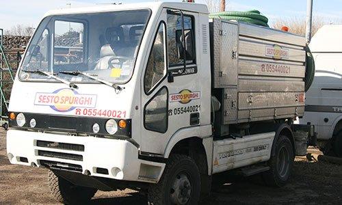 Un camioncino bianco visto di lato con un rimorchio di metallo, proprietario di Sesto Spurghi