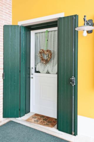 porta di entrata con persiane in legno aperte