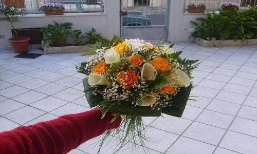 Ramo di Sposa con gigli bianchi,rose arance e gialle e un tocco verde