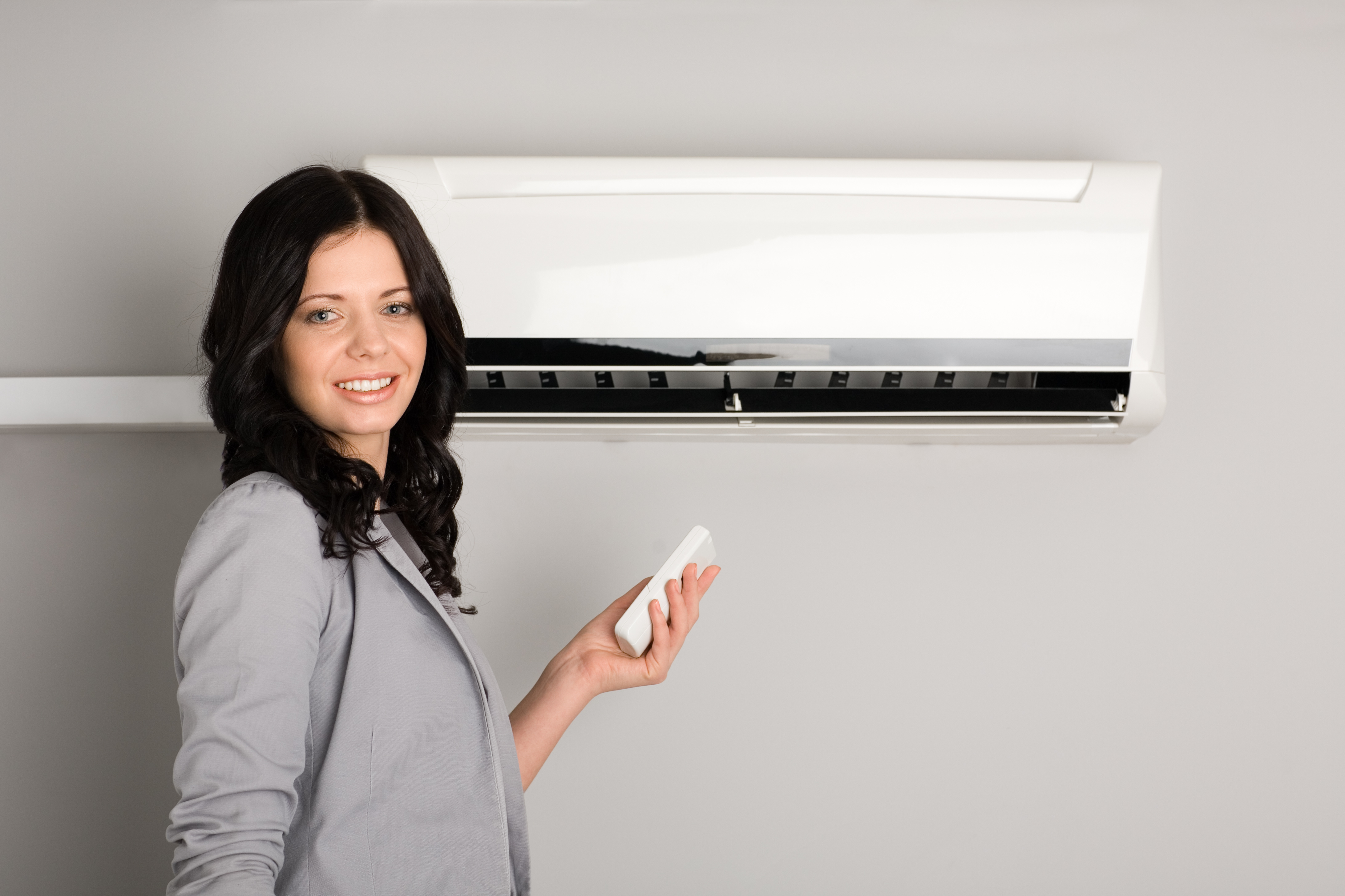 Woman with air conditioner remote