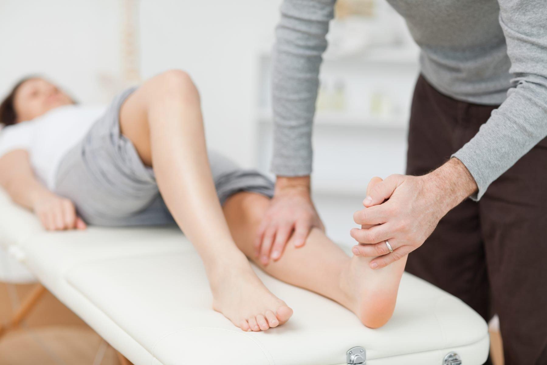 istruttore di massaggiare la gamba