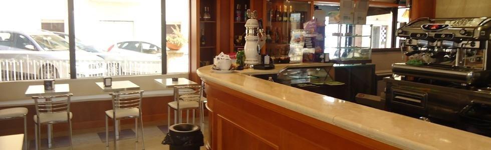 bancone di un bar con vista della macchina del caffe e  accanto dei tavoli e delle sedie