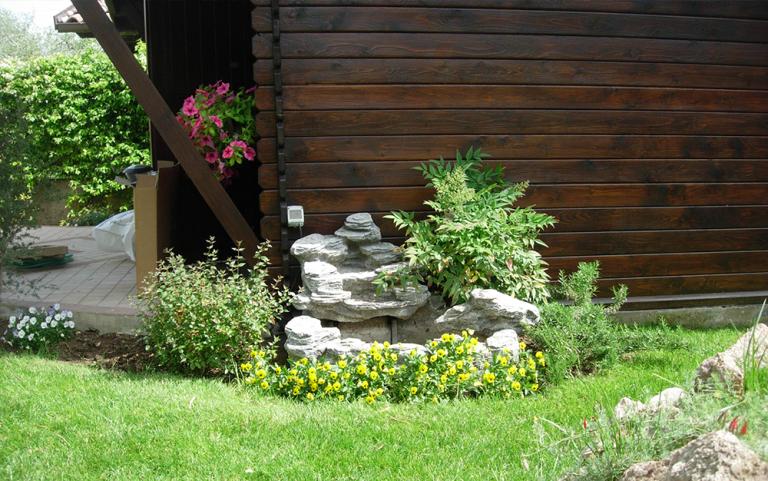 casetta in legno con a lato un recinto pieno di piante