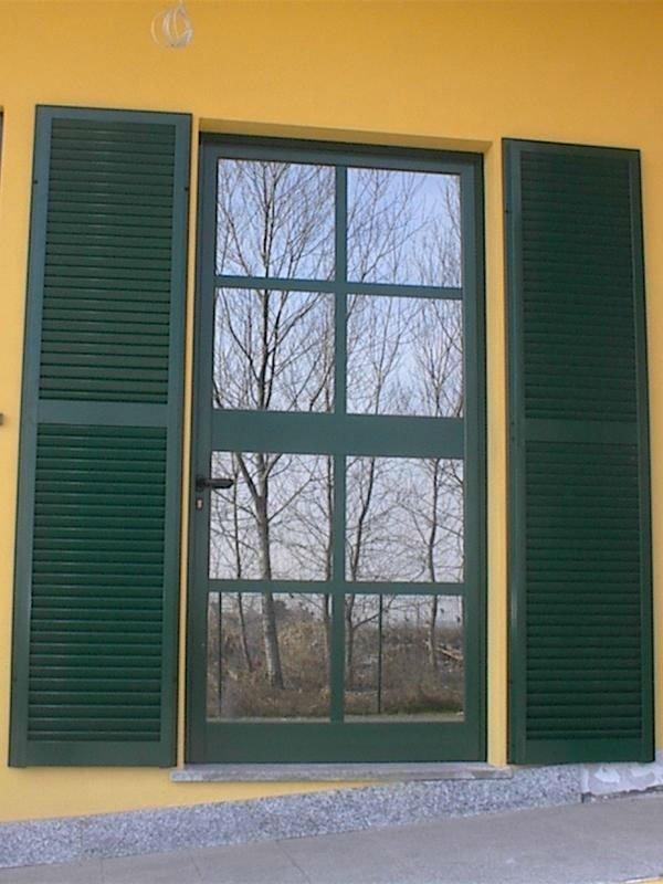 Porta verde di vetro e metallo con le controfinestre di metallo verde