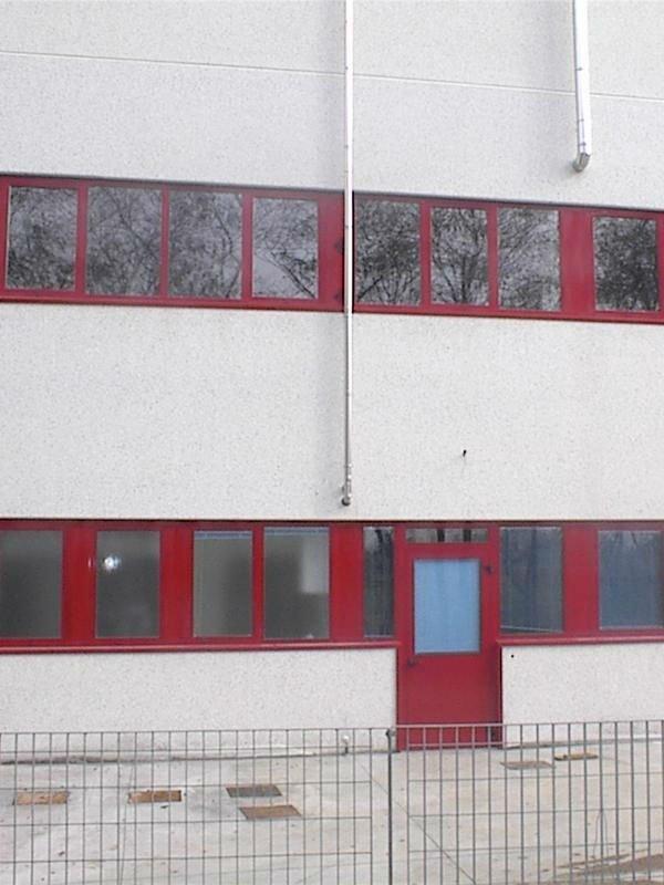 Due filiere di finestre con quadro di metallo rosso e nella inferiore ,la porta di accesso