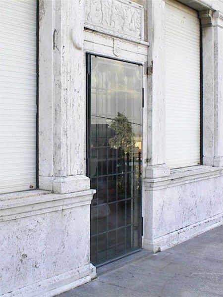 Porta di vetro coprendo la griglia di accesso a un antico edificio