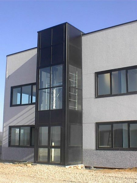 Colonna di metallo e vetro aggiunta alla capannone industriale