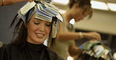 A woman having her hair coloured in a salon smiling