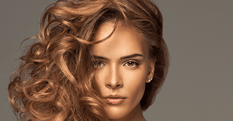 A brown haired female model with curly hair swept to the side