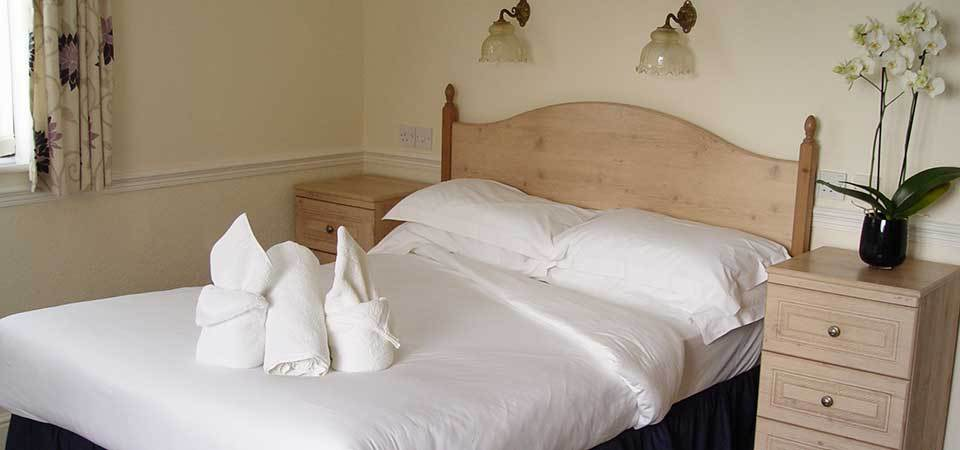 White towels neatly folded on bed, Jasminum room for booking