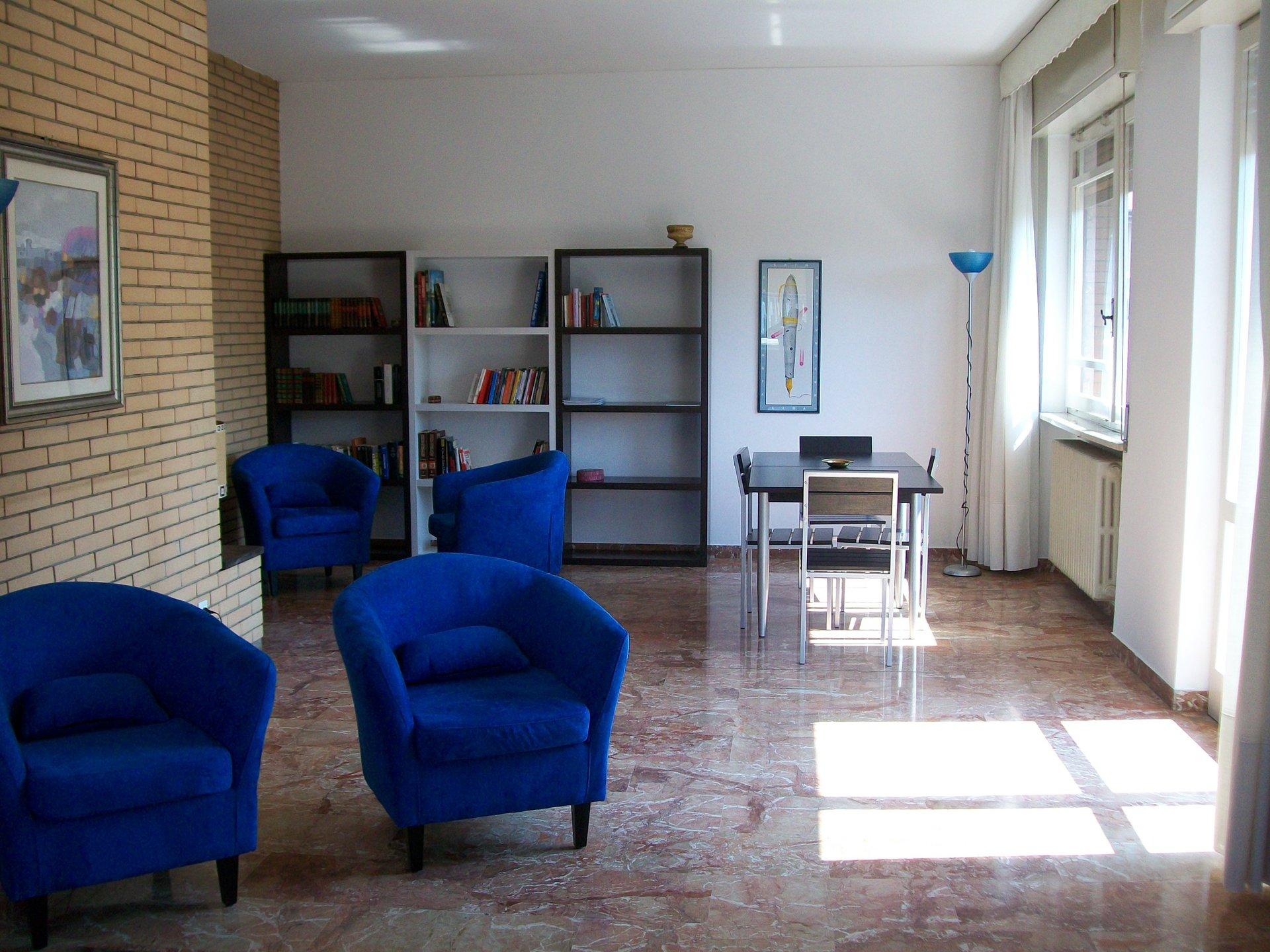 sala comune con poltrone e scaffali