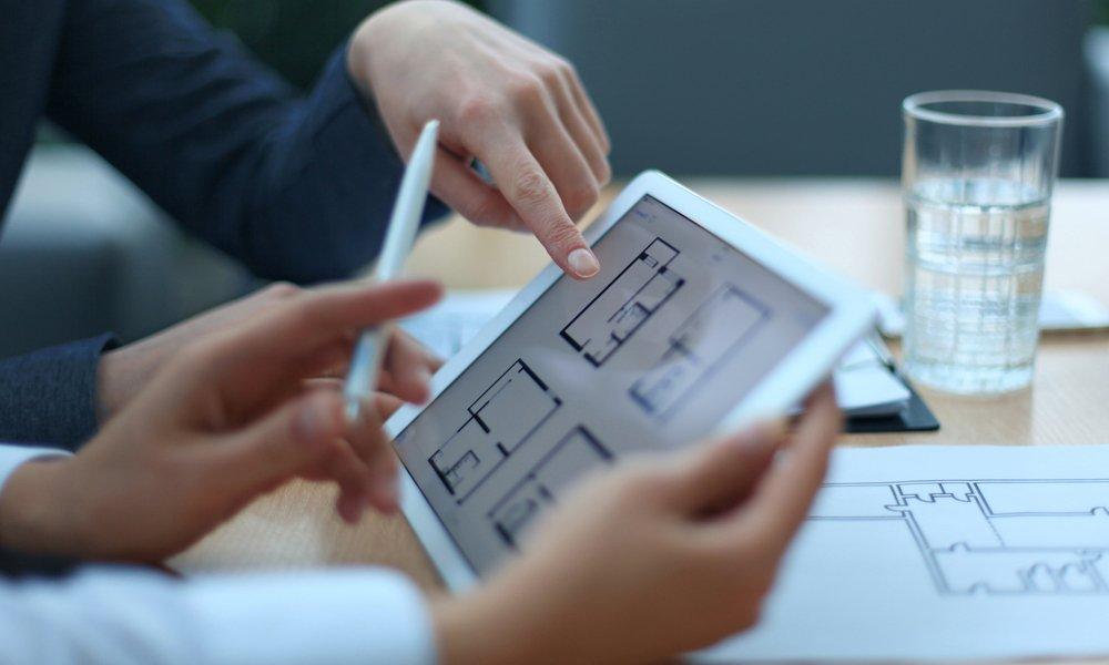 Consulente immobiliare mostra planimetria di un appartamento a un cliente