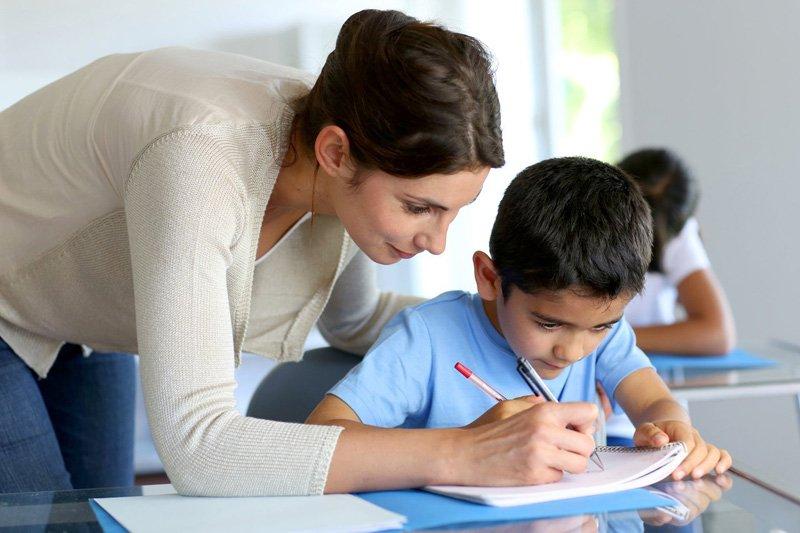 maestra insegna a un alunno