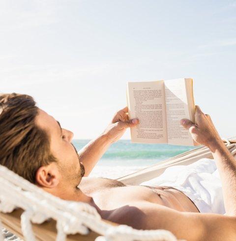 un uomo mentre legge un libro sdraiato su un amaca in spiaggia