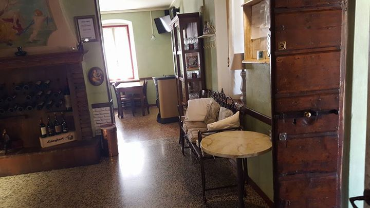 interno locale con camino e tavoli rotondi in legno