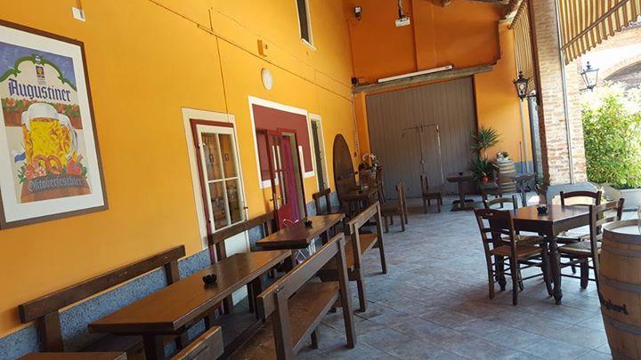 esterno locale con tavoli in legno e panche