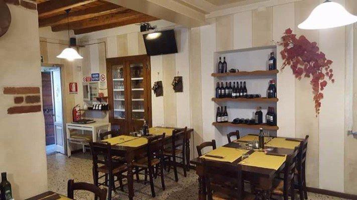 Interno del locale, travi di legno e bottiglie di vino