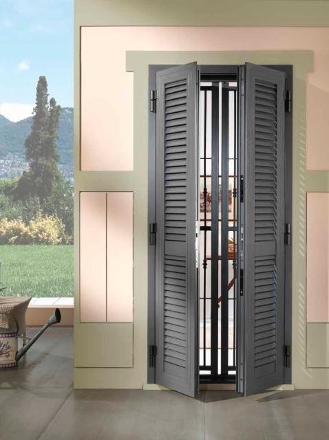 una finestra con tapparelle e delle griglie di color grigio