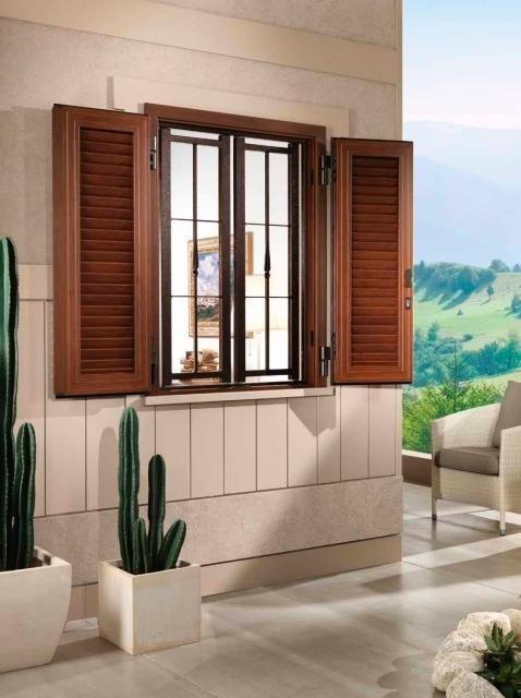 una finestra con tapparelle e delle griglie di color marrone