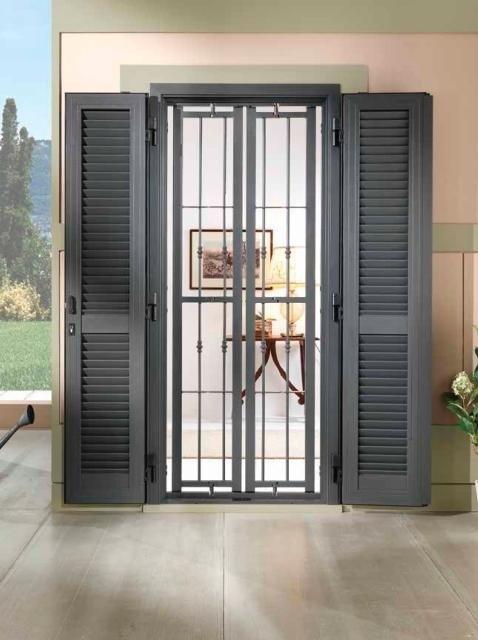 una finestra con griglie chiuse e tapparelle aperte
