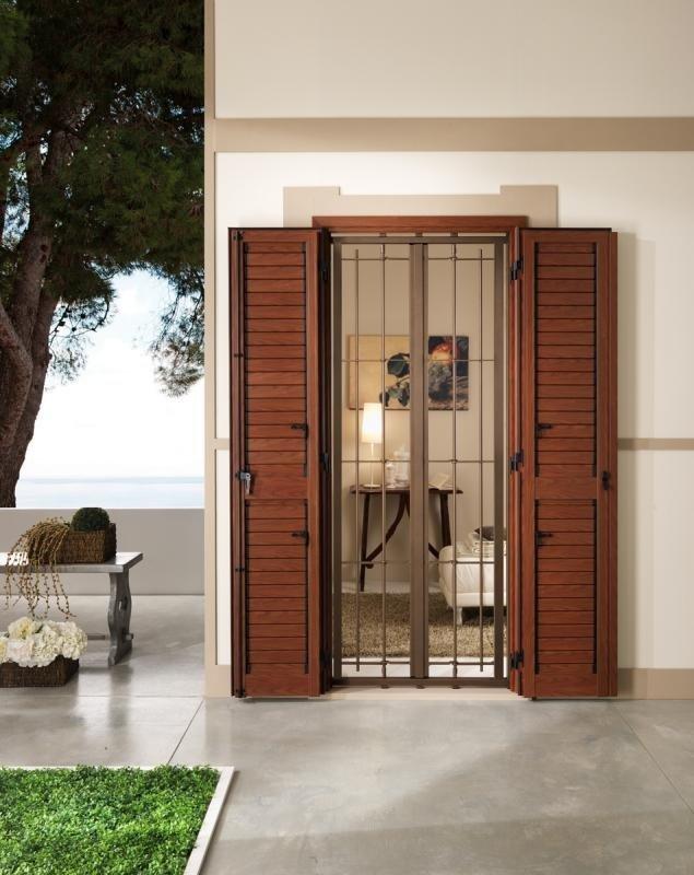 una finestra con delle tapparelle e griglie di color marrone e vista di una terrazza