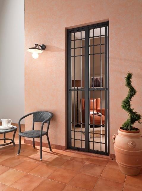 una finestra alta con una griglia e vista della terrazza
