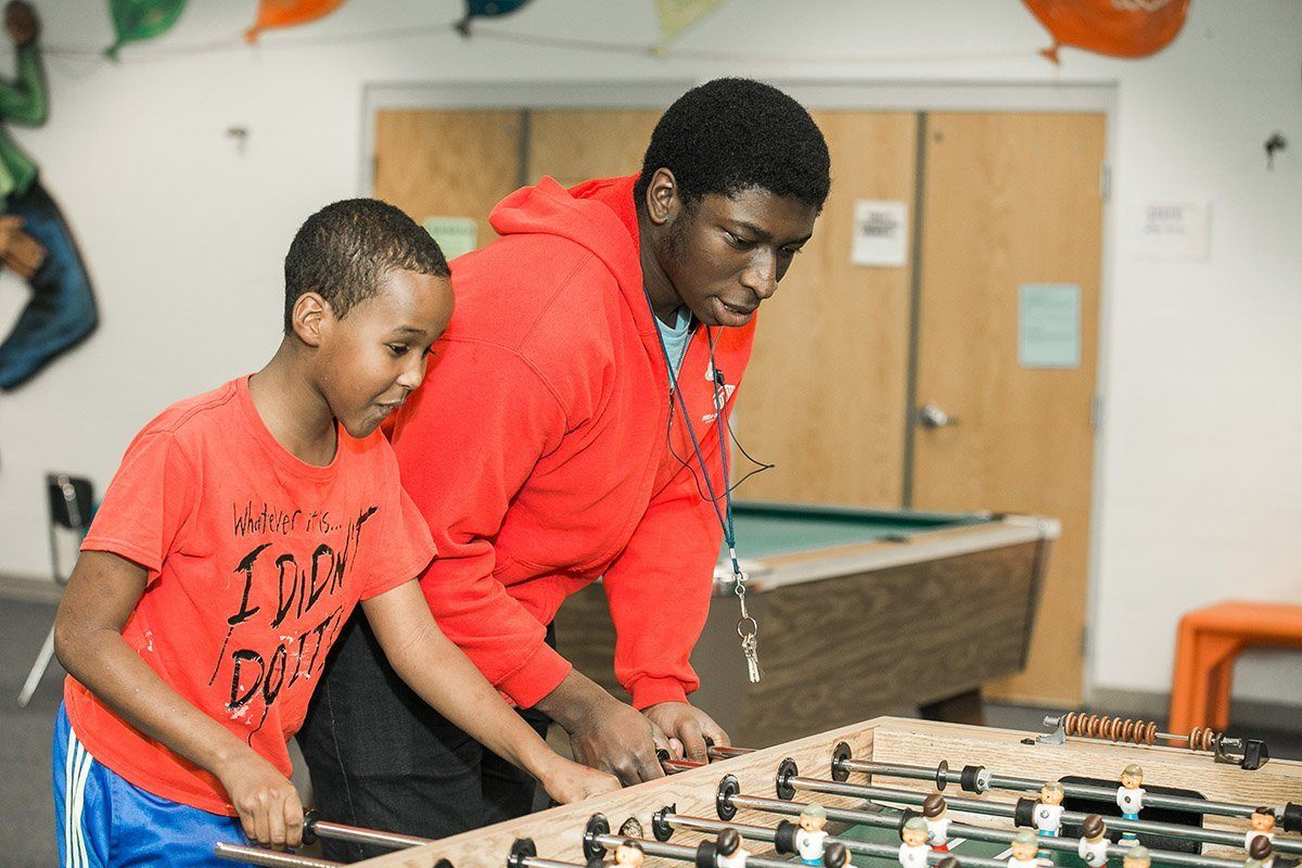 Adult male and boy playing foosball