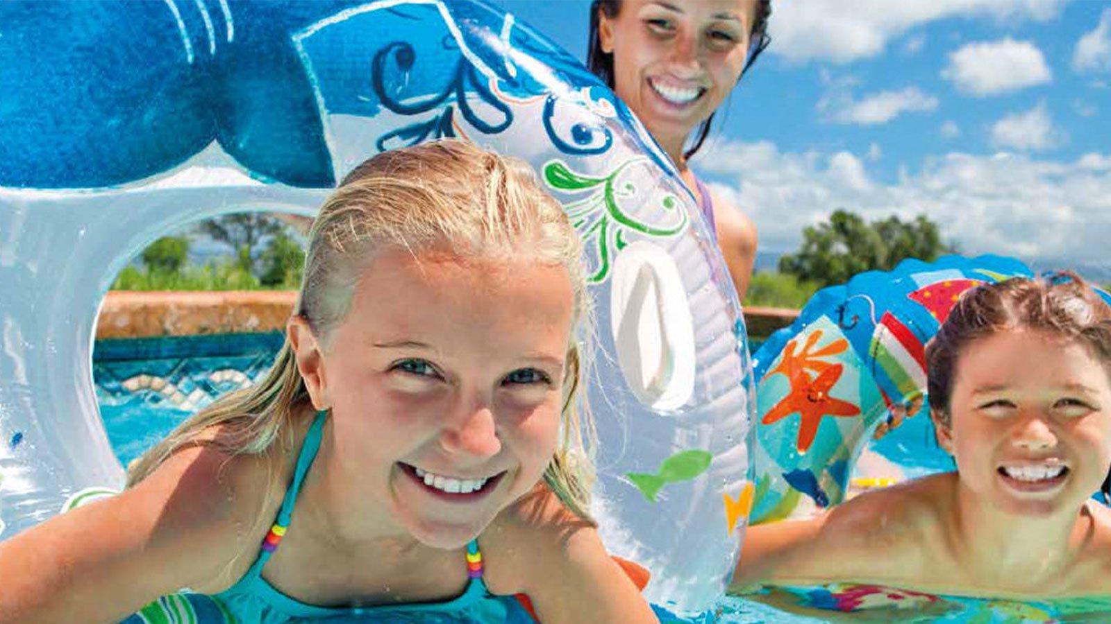 dei bambini con dei salvagenti colorati in piscina e dietro una ragazza