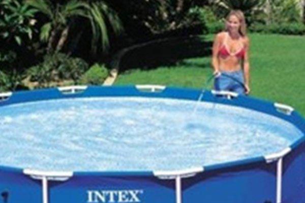 una donna che riempie con una canna una piscina rialzata Intex