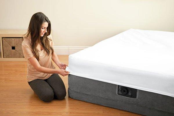 una ragazza che mette in lenzuola a un materasso ad acqua