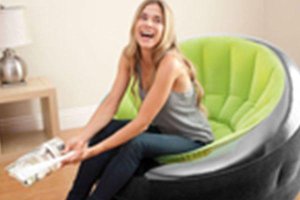 una ragazza seduta con un giornale in mano mentre ride