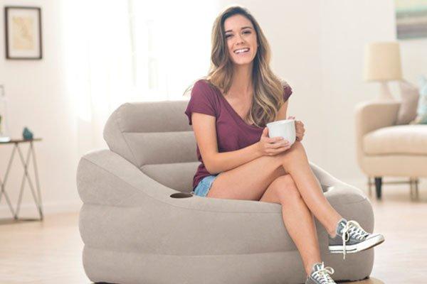 una ragazza seduta con una tazza in mano mentre