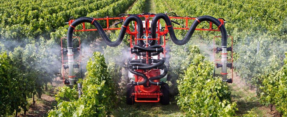 una macchina agricola che spruzza acqua in un vigneto