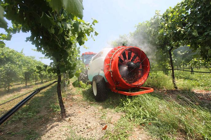 un macchinario agricolo con un motore con una ventola in un vigneto